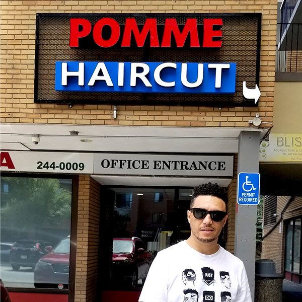 Pomme in front of Pomme Haircut barber shop